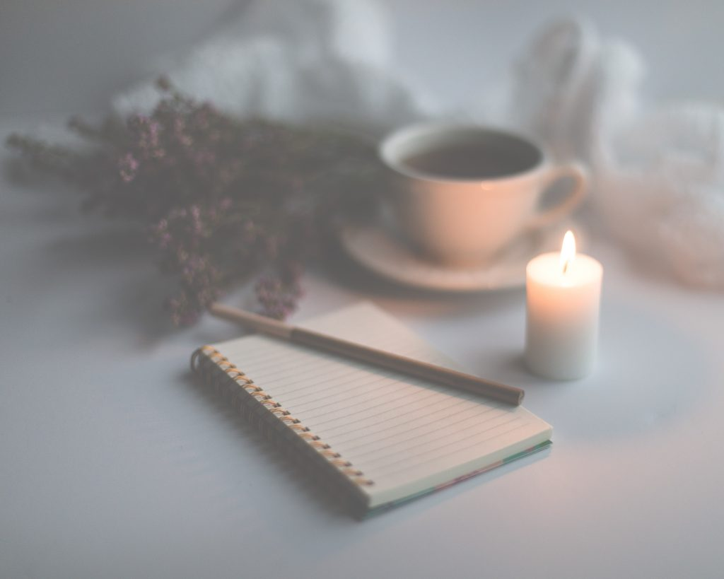 Writing paper and candle light set up for mindful journalling